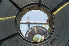 Coil's eye view. Looking through the center hole of a new coil of steel at another coil of steel in the background Royalty Free Stock Image