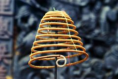 Coil Of Smoking Incense. A coil of smoking incense in a Buddhist temple in Vietnam. The tip of the coil with the ash has curled around. This incense coil, held royalty free stock photography