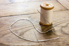 Coil with white threads and a needle stuck Stock Image