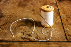 Coil with white threads and a needle stuck. Standing on an old wooden table royalty free stock images