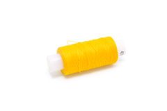 Coil of yellow threads. The coil of yellow threads for sewing on a white background royalty free stock photo