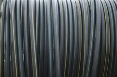 Coiled black hoses with stripes in different colors. Flexible tubes coiled up on a spool, made of black plastic with yellow and green stripes Stock Photography