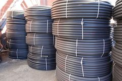 Coiled black plastic pipes stored outdoors. Coiled black plastic pipes stored outdoors stock photos