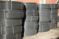 Coiled black plastic pipes stored outdoors.  royalty free stock images