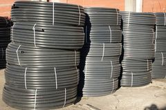 Coiled black plastic pipes stored outdoors.  stock image