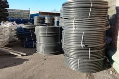 Coiled black plastic pipes stored outdoors.  stock photos