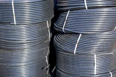 Coiled black plastic pipes stored outdoors.  stock photography