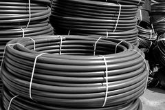 Coiled black plastic pipes stored outdoors.  Royalty Free Stock Photography