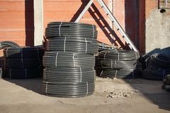 Coiled black plastic pipes stored outdoors.  royalty free stock photos