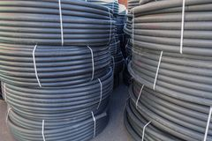 Coiled black plastic pipes stored outdoors.  royalty free stock image