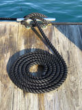 Coiled black rope on dock Stock Photography