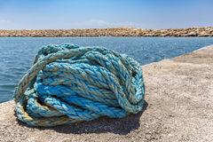Coiled blue mooring rope at water in greek cave Stock Photo