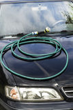 Coiled garden hose lies on the car`s hood. The Coiled garden hose lies on the car`s hood Stock Images