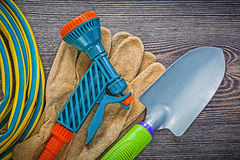 Coiled garden rubber hose leather safety gloves hand shovel on w. Ood board gardening concept stock photography