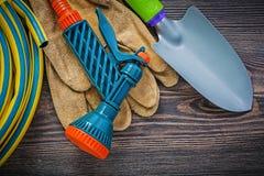 Coiled garden rubber hose protective gloves hand shovel on wood. Board gardening concept stock photos