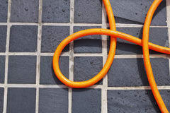 Coiled hose on tiles  Royalty Free Stock Photos
