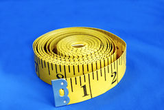 A coiled-like measuring tape isolated on blue. Background Royalty Free Stock Images
