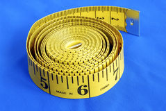 A coiled-like measuring tape isolated on blue Stock Photos