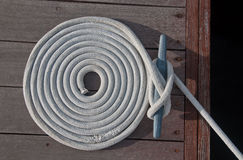 Coiled Line. White rope coiled on a wooden dock and tied to a metal dock cleat.  Cleats are used for securing docks and lines from boats Royalty Free Stock Images