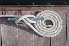 Coiled Line. White rope coiled on a wooden dock and tied to a metal dock cleat.  Cleats are used for securing docks and lines from boats Stock Photos