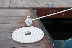 Coiled Line. White rope coiled on a wooden dock and tied to a metal dock cleat.  Cleats are used for securing docks and lines from boats Stock Photo