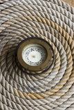 Coiled marine anchor line with antique compass Stock Image