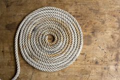 Coiled marine anchor line with old compass  Royalty Free Stock Photo