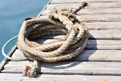 Coiled marine rope on wooden pier Royalty Free Stock Photo