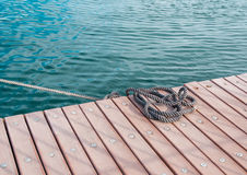 Coiled marine rope on wooden pier Stock Images