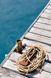 Coiled marine rope on wooden pier Stock Photo
