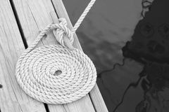Coiled mooring line. Black and white image of a coiled line tied around cleat on a wooden dock Royalty Free Stock Image
