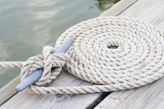 Coiled mooring line. Tied around cleat on a wooden dock Royalty Free Stock Images