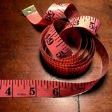 Coiled pink tape measure on weathered wood table. Royalty Free Stock Image