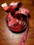 Coiled pink tape measure on weathered wood table. Royalty Free Stock Photos