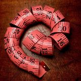 Coiled pink tape measure on weathered wood table. Stock Photo