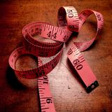 Coiled pink tape measure on weathered wood table. Stock Photography
