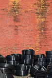 Coiled plastic pipes stored outdoors near the old red brick wall.  Royalty Free Stock Image