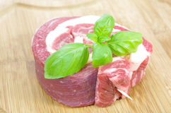 Coiled raw beef with basil. On cutting board Stock Image