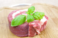 Coiled raw beef with basil. On cutting board Stock Images