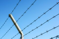 Coiled razor wire with its sharp steel barbs on top of a mesh perimeter fence ensuring safety and security. Preventing access or the escape prisoners, blue sky Stock Image