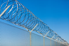 Coiled razor wire on top of a fence. Coiled razor wire with its sharp steel barbs on top of a wire mesh perimeter fence ensuring safety and security, preventing Royalty Free Stock Image