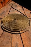 Coiled rope. Coiled brown rope in the bright sun on the deck Royalty Free Stock Photography