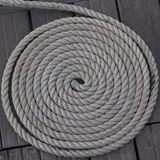 Coiled rope. On a wooden pier Stock Image