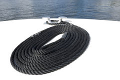 Coiled rope on a boat. Black nylon mooring line or rope coiled on the deck at the bow of a boat royalty free stock image