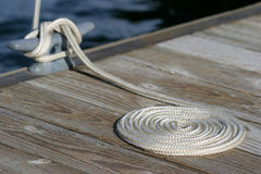 Coiled rope and cleat. A neatly coiled rope leading to the cleat and a moored sailboat in yellowstone national park, wyoming Stock Image