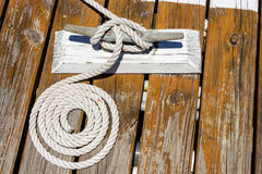 Coiled rope on deck. Coiled rope on wooden deck with cleat and cleat hitch Royalty Free Stock Images