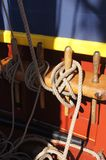 Coiled rope lines stored on belaying pins. On a wooden tall ship Royalty Free Stock Images