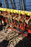 Coiled rope lines stored on belaying pins. On a wooden tall ship Royalty Free Stock Image