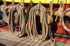 Coiled rope lines stored on belaying pins. On a wooden tall ship Stock Images