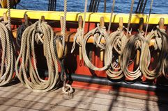 Coiled rope lines stored on belaying pins. On a wooden tall ship Stock Photography